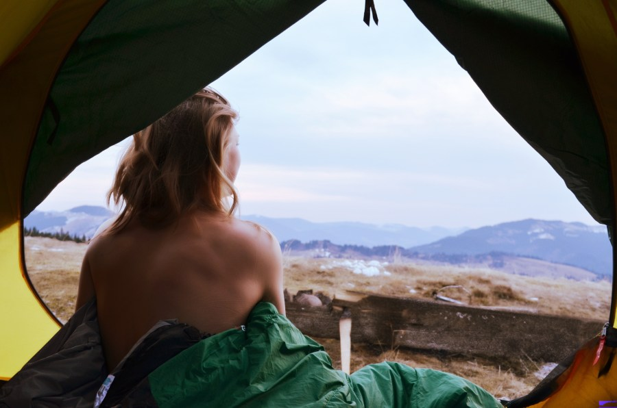 A young woman sitting in the tent with naked back, looking at the mountain landscape in winter