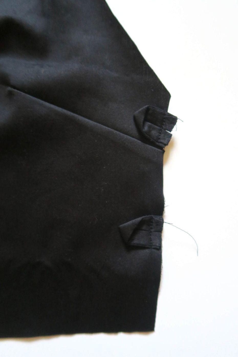 Colocando los bucles en el costado del cuerpo de vestido mini con espalda al aire