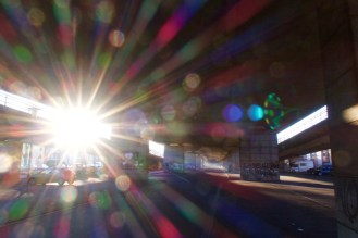 An einem späten Nachmittag im Dezember scheint die Sonne unter der Nordbrücke und zaubert viele bunte Lens Flares ins Foto.