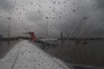 Regen perlt am Flugzeugfenster beim Rollen auf die Startbahn