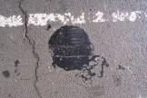Ein Teerfleck mit alter Markierungslinie auf der Straße