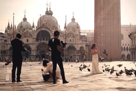 Früh morgens machen viele auf dem leeren Markusplatz Hochzeitsfotos