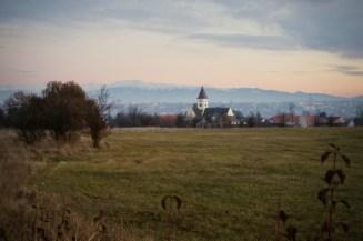Wiesen, Hecken und eine kleine Kirche mit den Karpaten im Hintergrund