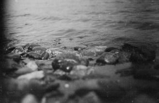 Murmelnde kleine Wellen mit Kieseln am Rheinufer