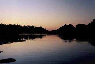 Wasser und Silhouetten der Felsen und Palmen Abends am Fluss in Hampi