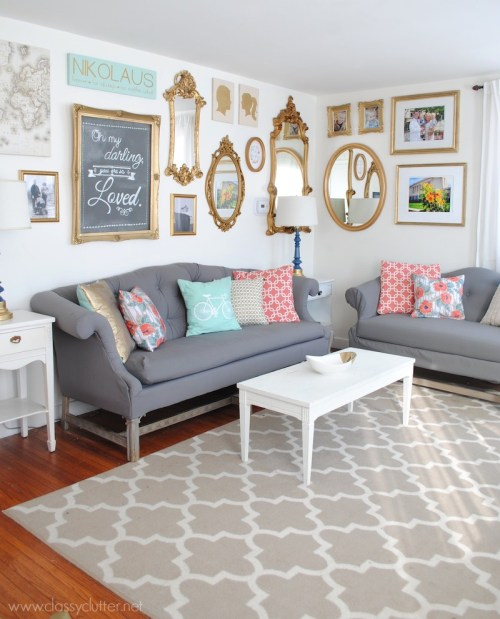 Typography Interior Design Wall Gallery Gold Mirrors Framed Wall Art Rug Hardwood Floors Gray Couches White Coffee Table