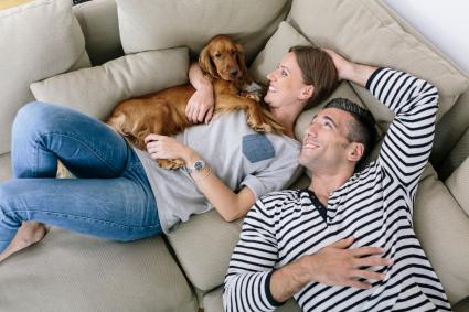 Happy couple on couch with dog
