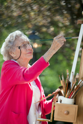 Senior woman painting a canvas