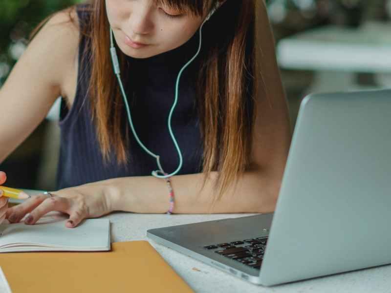 woman in blue tank top using macbook pro
