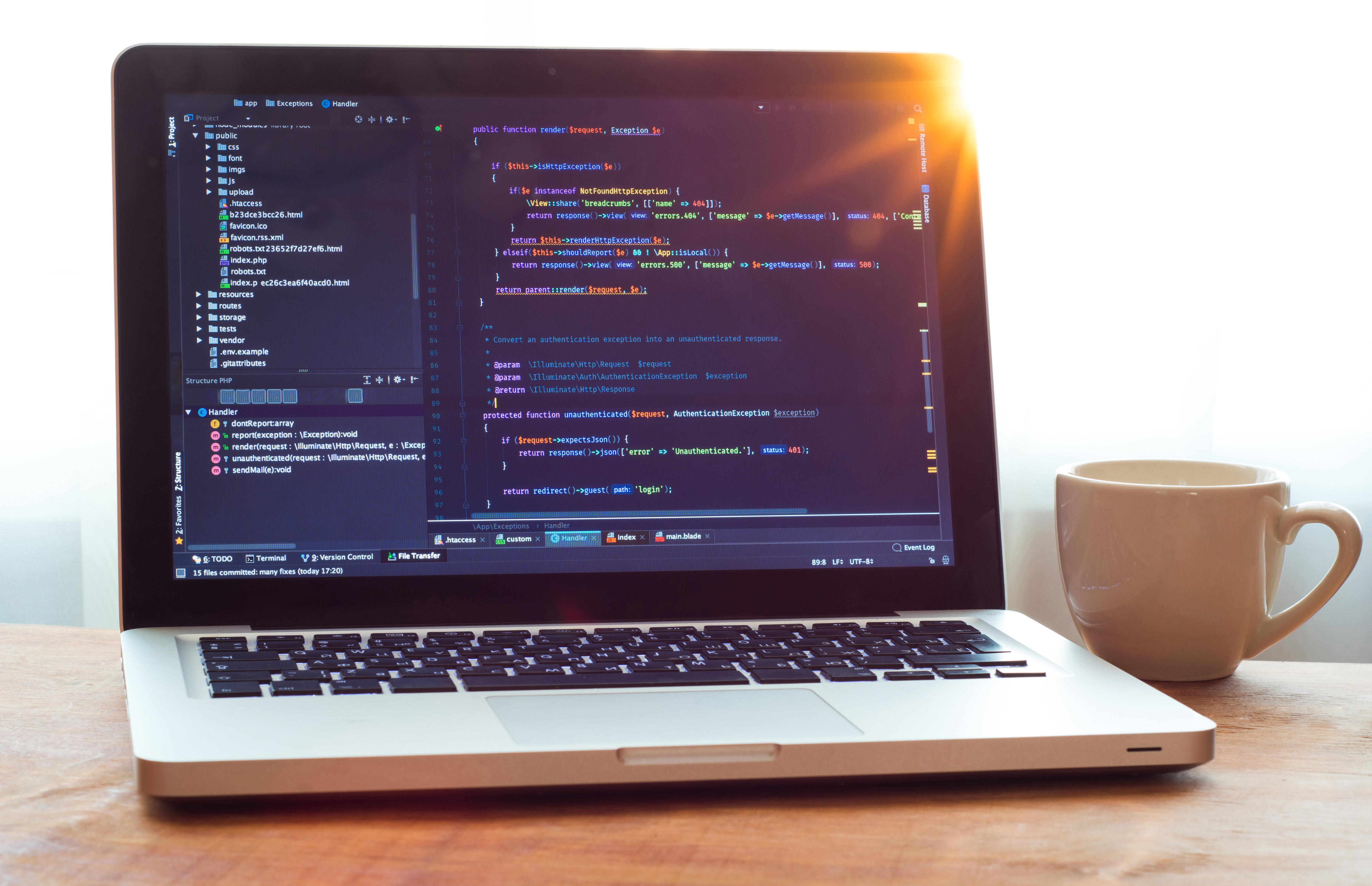 Computer code on laptop (web developing) and white mug in sunlight, working place