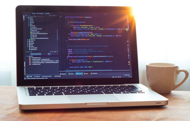 Php code on laptop (web developing) and white mug in sunlight