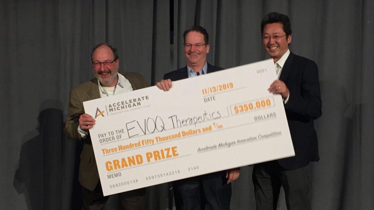 EVOQ team holding their prize check at Accelerate Michigan competition 2019