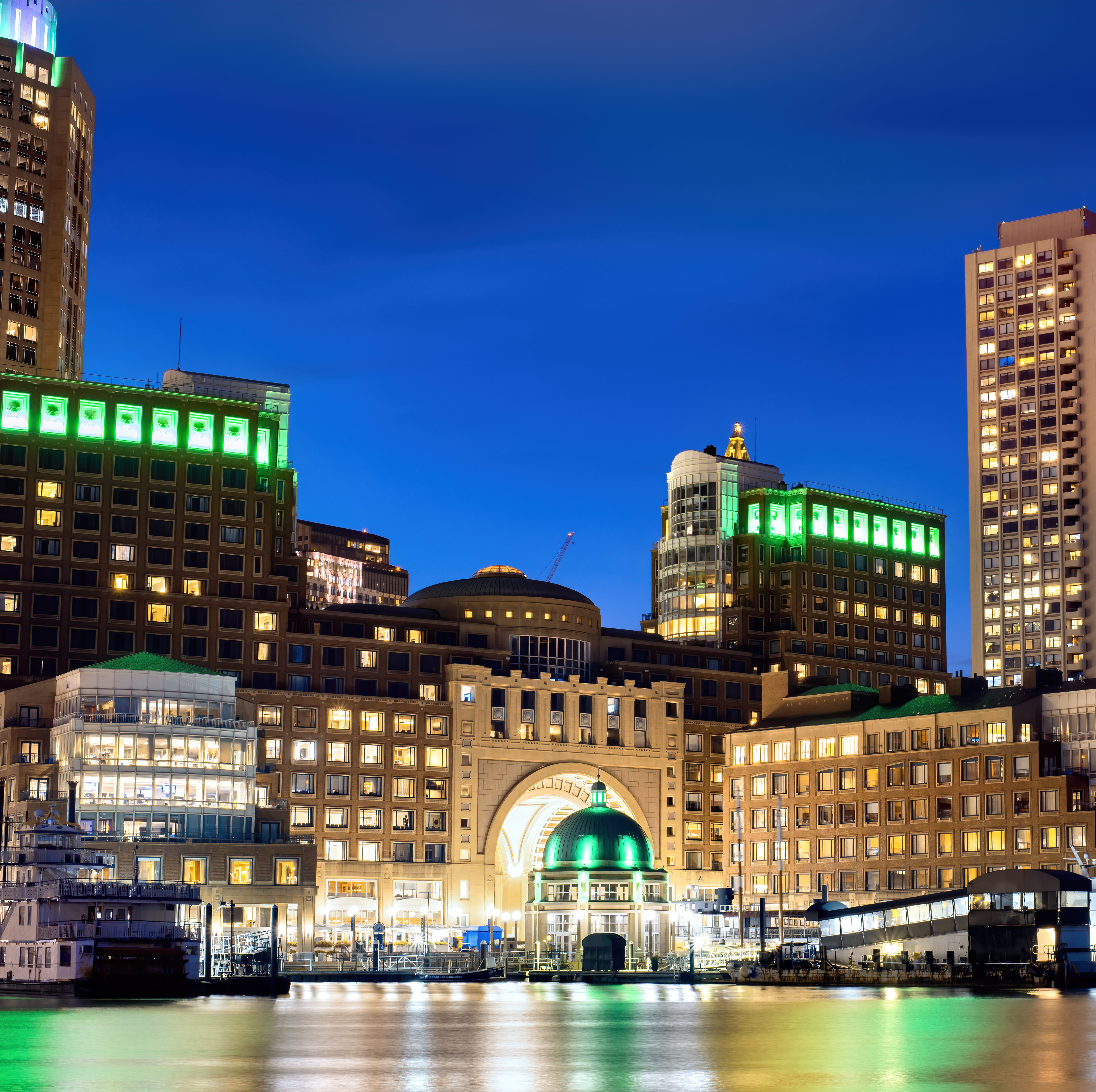 View of Boston downtown at night, water and seaport on the foreground, multiple nightlights, USA