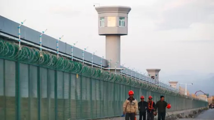 Workers walk along the fence of a likely detention center for Muslims in Xinjiang Province.