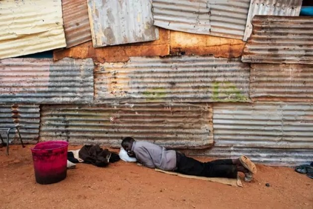 A Zimbabwean man rests outside a church at an informal migrant camp in Musina, South Africa.