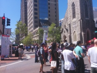Crowds watch dancers and other performers at the intersection of Laura and Monroe Streets as OneSpark rolls on.