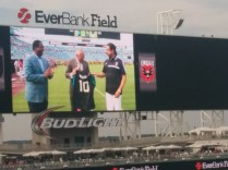 Happy birthday! Fulham coach Felix Magath receives a commemorative jersey from Jacksonville mayor Alvin Brown and Jaguars owner Shad Khan.