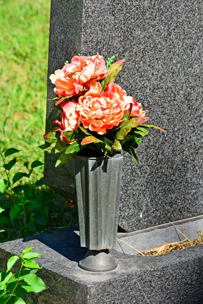 Memorial vase at base of headstone