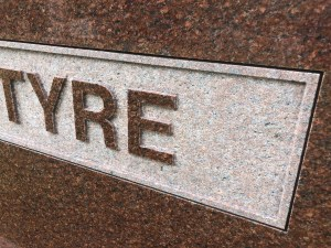 Close up on raised polished lettering done on a Wausau Red granite monument