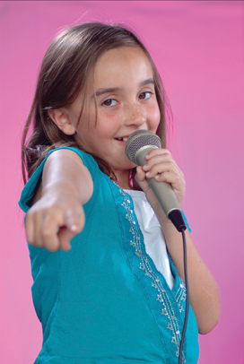 Image of a young girl singing and pointing to her audience