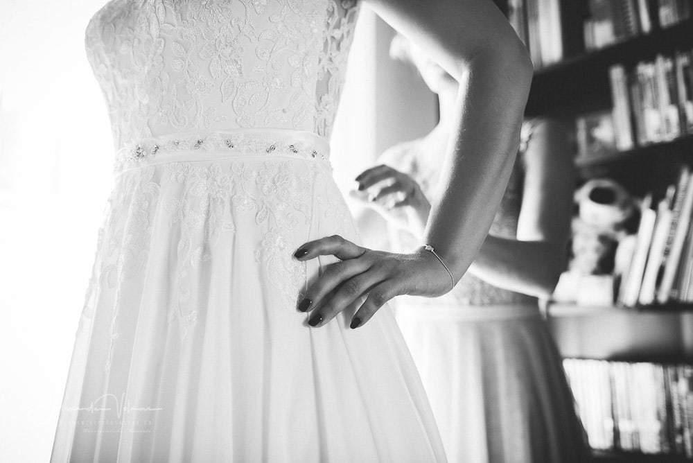 Hochzeitsfotograf fotografiert letzten Schliff am Hochzeitskleid