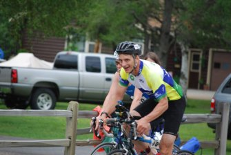 Chad Couto rides a bicycle outdoors during a marathon.