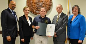 Evan Dominick, a nine-year Chester County employee, holds the proclamation for . He is flanked by Commissioner Terence Farell (from left), Commissioner Michelle Kichline, Deputy Director of 9-1-1 Operations John Haynes, and Commissioner Kathi Cozzone.