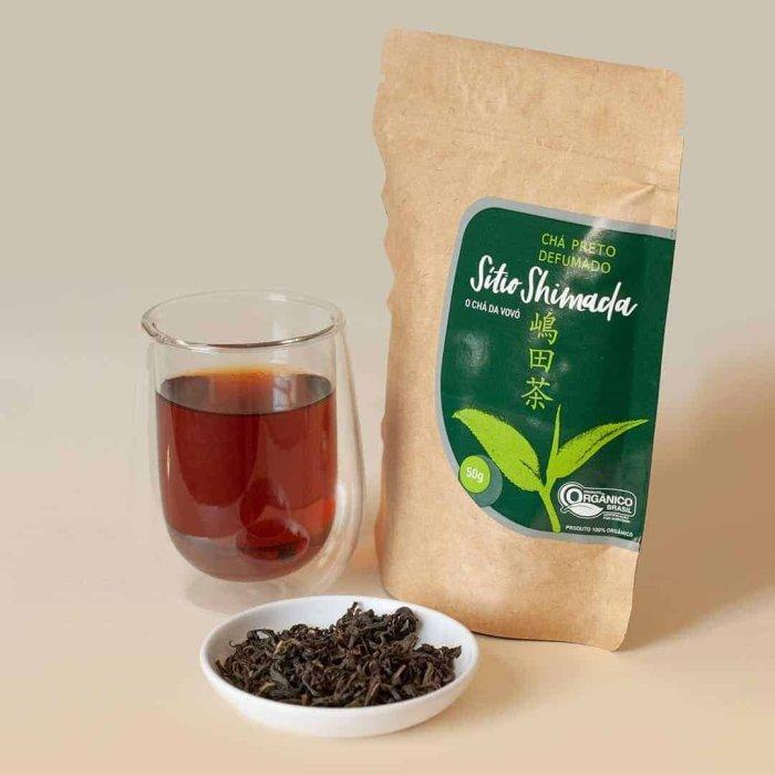 O chá preto inficionado em um copo de vidro duplo, as folhas de chá em um pequeno recipiente e a embalagem do chá.