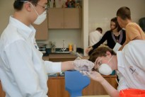 Student helps friend with molding alginate