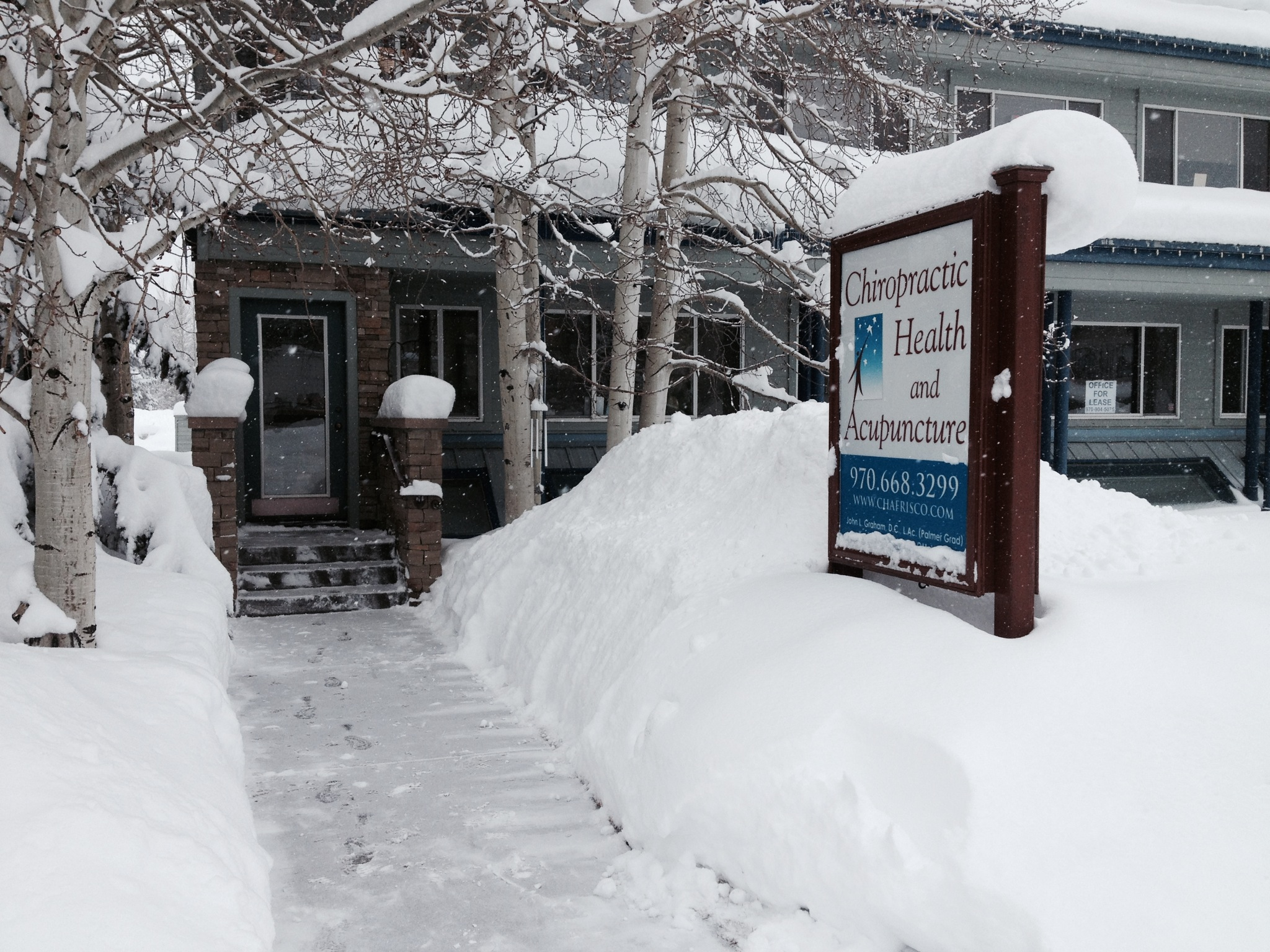 Many feet of snow in front of the chiropractic health and acupuncture office entrance