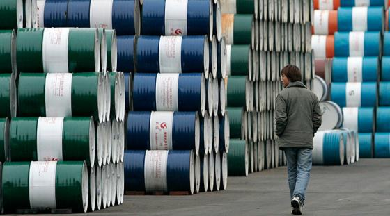 A man walks past a storage area for oil barrels in Shanghai January 20, 2007. China will delay reporting how far short it fell on official energy efficiency targets until it has tightened up the system used to calculate consumption, the official Xinhua agency said. REUTERS/Aly Song (CHINA) - RTR1LE0U