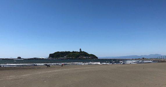 線路を渡った先、突き当りにある海岸の向こうに江の島が見える