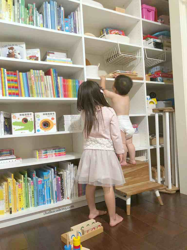 Closet shelf with books in English, Chinese, and Korean plus Montessori materials