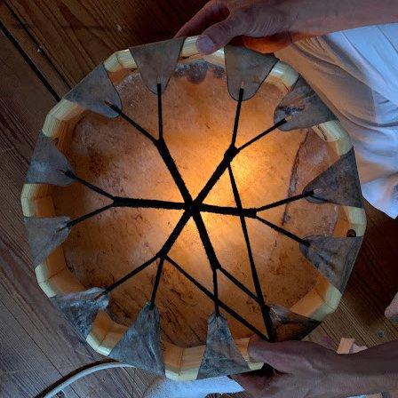 Un tambor chamánico templándose bajo la luz de una vela