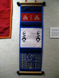 (Cotton and metallic threads, 2007 - Loaned by Michael Schuster and Gayle Goodman) Both the pillow case and the caddy are hand woven with ancient images but are made for contemporary use. The pillow case is woven with an image of Skanda, god of war in Hinduism. The contemporary pocket holder re-employs old symbolism and patterns: a red temple design; dancers who could be stylized apsaras; Skanda, god of war in Hinduism, and a Naga.