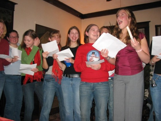 "This picture is ridiculous, but I have to include it, because it basically sums up...everything. Here's a line of 7 tipsy undergraduates in various shades of denim and....Katie, in a satin blouse. And gaucho pants. Singing a solo. This was an English department parody of the 12 Days of Christmas. Katie was singing ""Fiiiiiiiiiiiiive gooooooolden boooooooks!"" Natch."