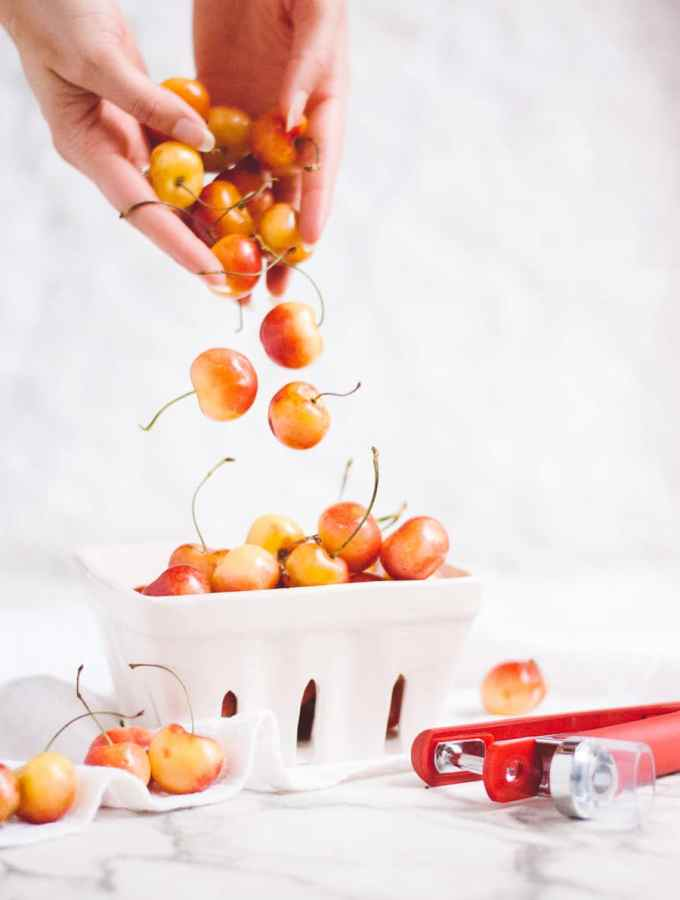 hands hodding yellow cherries into a bowl