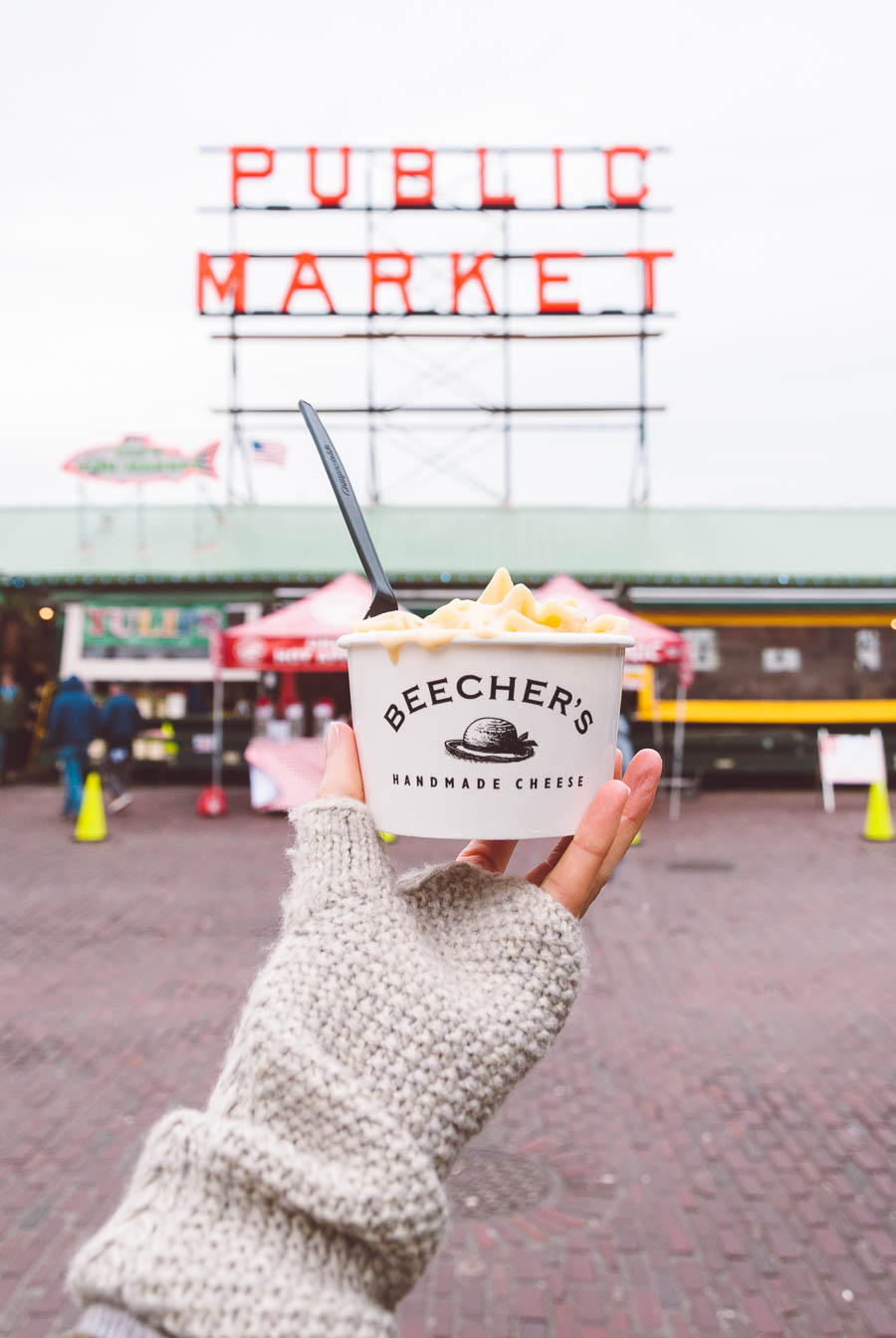 A hand holding a white cup of Beecher's Mac and Cheese in front of the Pike Market sign in Seattle