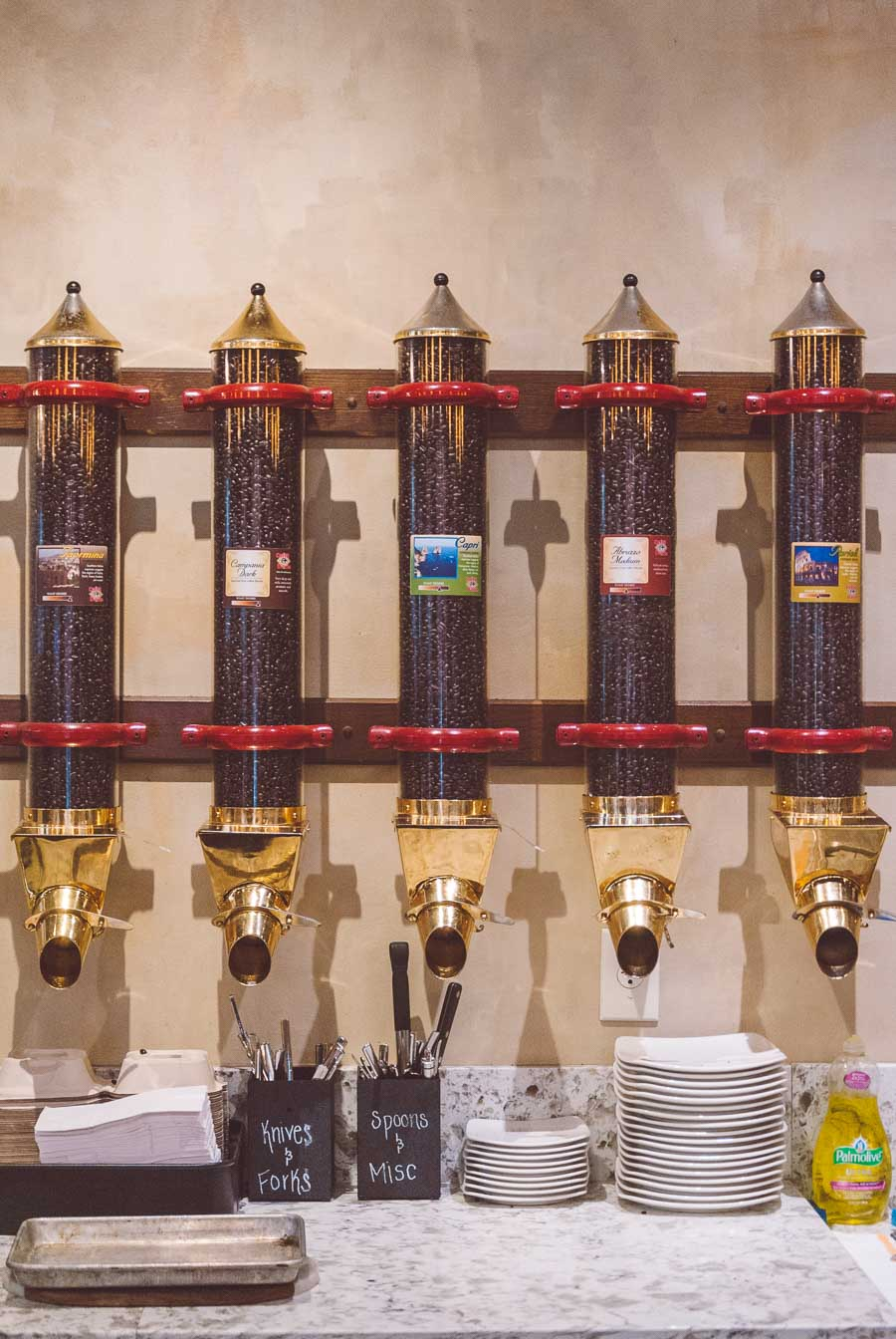 Wall mounted coffee bean holders lined up at Caffe d'arte