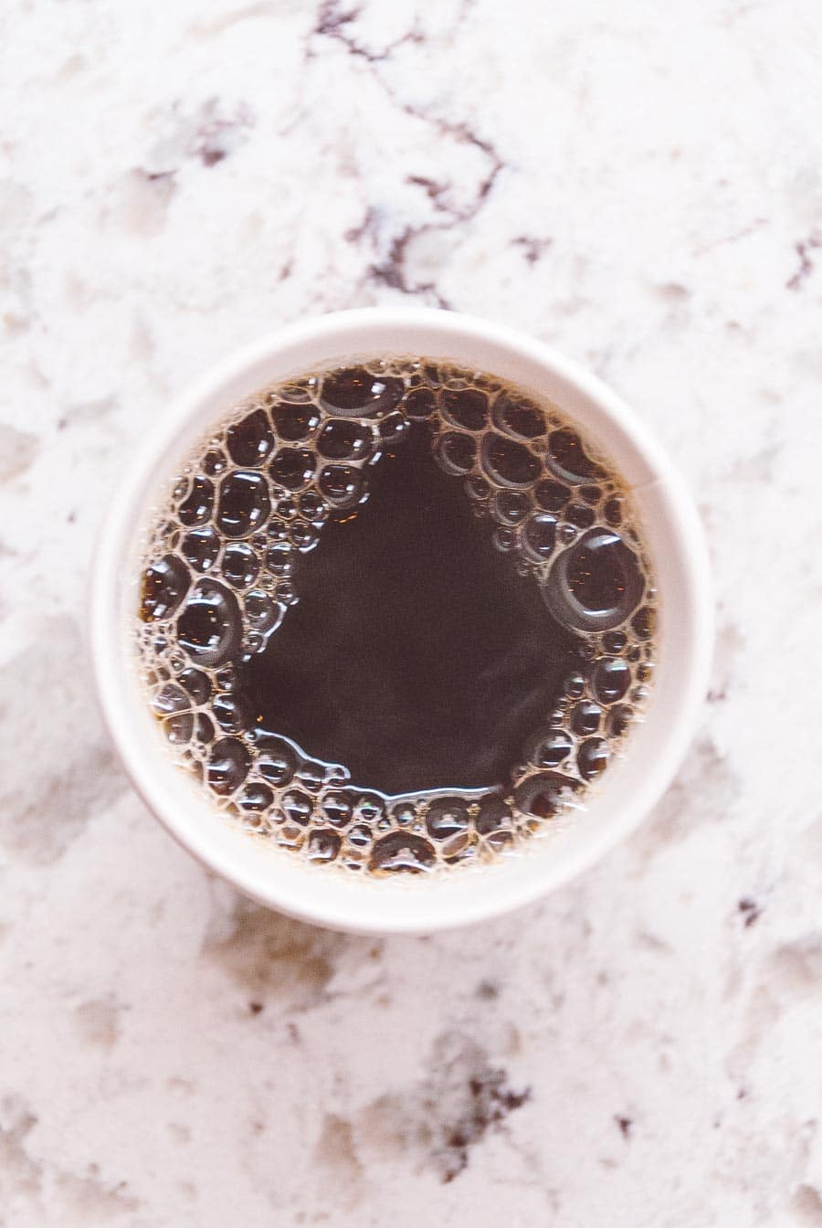 overhead shot of a cup of coffee with a white marble background