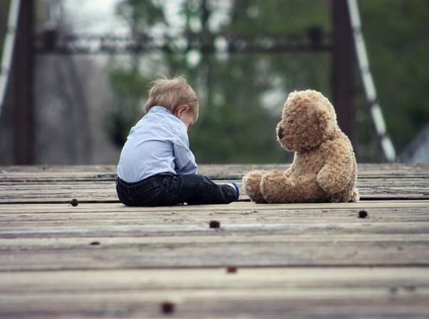 boy-playing-with-teddy-bear-on-wooden-bridge.jpg