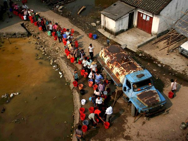 Villagers queue for a chance to fill containers with fresh drinking water, delivered by truck to the dry villages of south China's Guangdong Province. Photo: AP via National Geographic