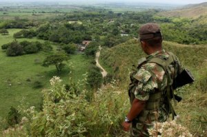 A FARC rebel stands guard on a hill in Montealegre Colombia.  Credit: Juan B. Diaz/AP