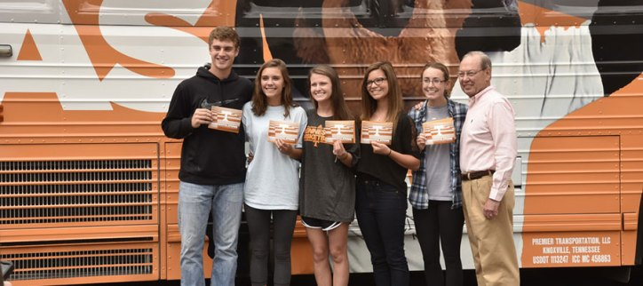 Chancellor Cheek and the newly admitted Volunteers from Dobyns-Bennett High School in front of the Big Orange Bus.