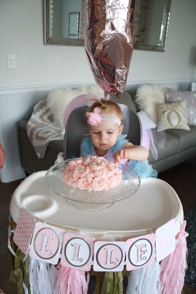 Easy first birthday ideas: birthday girl enjoys smash cake