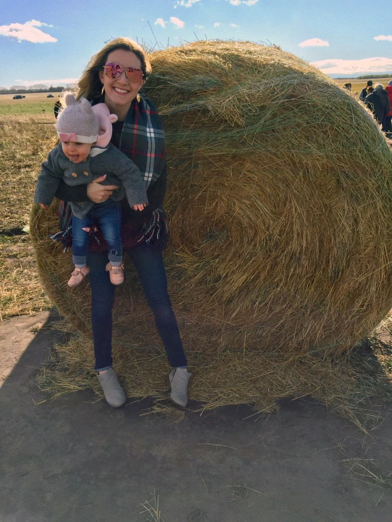 New mom and baby enjoy hay bale