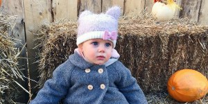 Baby sits on hay bale