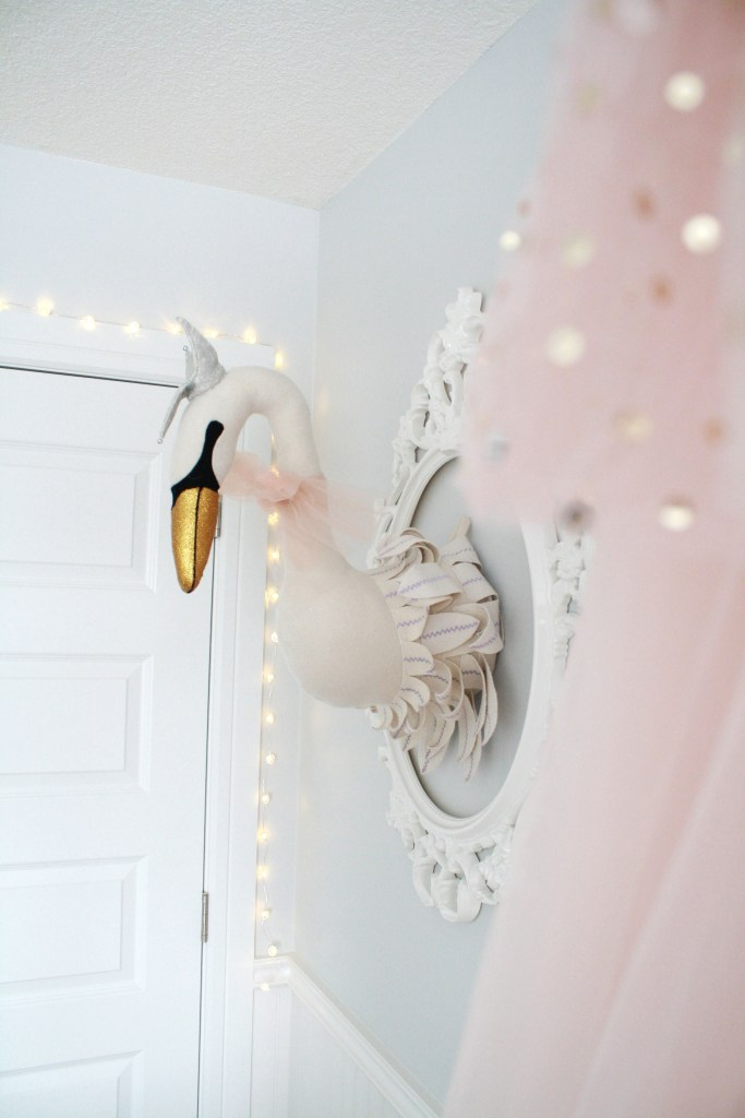 Pink and gray nursery with plush taxidermy-style swan head
