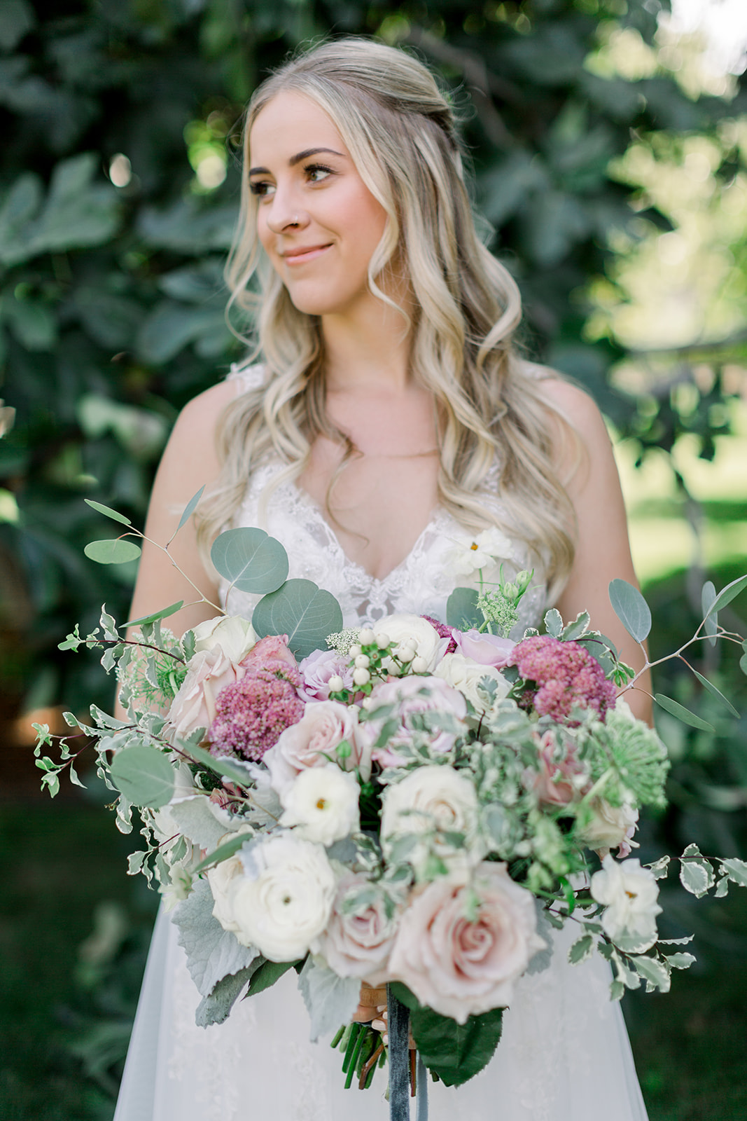 CH&LER bride holding a soft blush and blue tone bouquet
