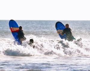 Surf instructors helping beginner surfers in Legian, Bali
